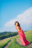 Portrait of a beautiful young woman in a red dress on a background of sky and grass in summer. Beautiful young happy woman in long red dress dreams in green Royalty Free Stock Image