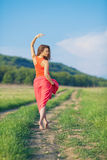 Portrait of a beautiful young woman in a red dress on a background of sky and grass in summer. Beautiful young happy woman in long red dress dreams in green Royalty Free Stock Photography