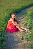 Portrait of a beautiful young woman in a red dress on a background of sky and grass in summer. Beautiful young happy woman in long red dress dreams in green Stock Photography