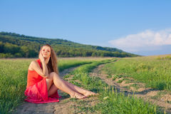 Portrait of a beautiful young woman in a red dress on a background of sky and grass in summer Royalty Free Stock Photography