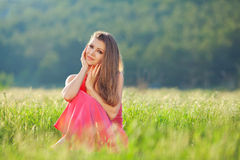 Portrait of a beautiful young woman in a red dress on a background of sky and grass in summer. Beautiful young happy woman in long red dress dreams in green Royalty Free Stock Images