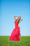 Portrait of a beautiful young woman in a red dress on a background of sky and grass in summer. Beautiful young happy woman in long red dress dreams in green Royalty Free Stock Photo