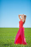 Portrait of a beautiful young woman in a red dress on a background of sky and grass in summer Royalty Free Stock Image