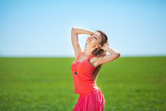 Portrait of a beautiful young woman in a red dress on a background of sky and grass in summer Royalty Free Stock Photos