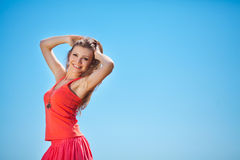 Portrait of a beautiful young woman in a red dress on a background of sky and grass in summer Stock Photography