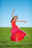 Portrait of a beautiful young woman in a red dress on a background of sky and grass in summer. Beautiful young happy woman in long red dress dreams in green Royalty Free Stock Photos