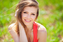 Portrait of a beautiful young woman in a red dress on a background of sky and grass in summer Royalty Free Stock Images