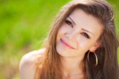 Portrait of a beautiful young woman in a red dress on a background of sky and grass in summer Stock Image