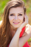 Portrait of a beautiful young woman in a red dress on a background of sky and grass in summer Royalty Free Stock Photo
