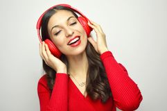 Portrait of beautiful young woman red dressed enjoying listening to music with closed eyes on white background.  Stock Photo