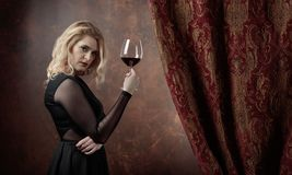Portrait of beautiful young woman with red wine. Gorgeous hair and natural makeup. Fashion beauty photo. Natural blonde in black dress Royalty Free Stock Image