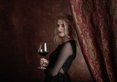Portrait of beautiful young woman with red wine. Gorgeous hair and natural makeup. Fashion beauty photo. Natural blonde in black dress Royalty Free Stock Photography