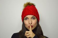 Portrait of beautiful young woman with red wool hat showing silence gesture over gray background stock images