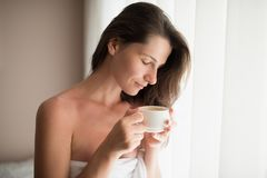 Portrait of beautiful young woman relaxing at cozy home atmosphe. Re next to window. Attractive woman wearing white towel with cup of hot chocolate or coffee in Stock Images