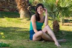 Portrait of beautiful young woman relaxing on grass with palm tr Royalty Free Stock Photography