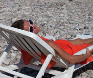 Portrait of beautiful young woman relaxing in sunbed Royalty Free Stock Image