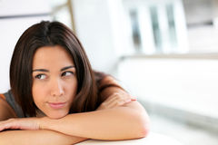 Portrait of beautiful young woman relaxing on table. Portrait of brunette with bored look stock photography