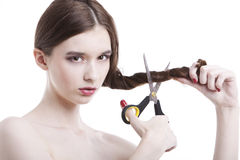 Portrait of beautiful young woman with scissors cutting her hair over white background royalty free stock photography