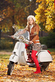 Portrait of beautiful young woman on scooter Stock Image