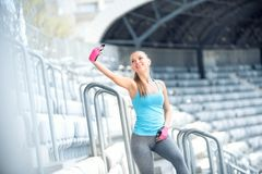 Portrait of beautiful young woman selfie with a smartphone. Modern concept of fitness life Stock Photography