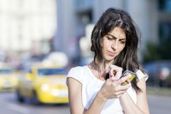 Portrait of beautiful young woman sending messages. Portrait of beautiful brunette  woman talking on the phone on the street Royalty Free Stock Image