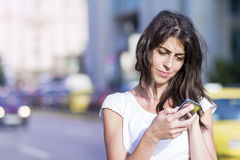 Portrait of beautiful young woman sending messages. Portrait of beautiful brunette  woman talking on the phone on the street Royalty Free Stock Images