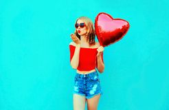 Portrait beautiful young woman sending sweet air kiss with red heart shaped balloon on colorful blue stock images