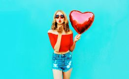 Portrait beautiful young woman sending sweet air kiss with red heart shaped balloon on colorful blue stock photos