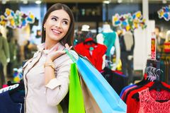 Portrait of beautiful young woman with shopping bags in clothing. Portrait of beautiful young woman with shopping bags going out on a shopping spree Stock Photography