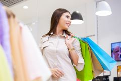 Portrait of beautiful young woman with shopping bags in clothing. Portrait of beautiful young woman with shopping bags going out on a shopping spree Royalty Free Stock Photos