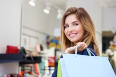 Portrait of beautiful young woman with shopping bags in clothing. Portrait of beautiful young woman with shopping bags going out on a shopping spree Royalty Free Stock Images