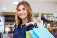 Portrait of beautiful young woman with shopping bags in clothing. Portrait of beautiful young woman with shopping bags going out on a shopping spree Stock Image