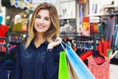 Portrait of beautiful young woman with shopping bags in clothing. Portrait of beautiful young woman with shopping bags going out on a shopping spree Royalty Free Stock Photography