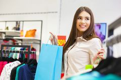 Portrait of beautiful young woman with shopping bags in clothing. Portrait of beautiful young woman with shopping bags going out on a shopping spree Stock Images