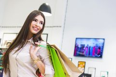 Portrait of beautiful young woman with shopping bags in clothing. Portrait of beautiful young woman with shopping bags going out on a shopping spree Stock Photos