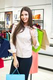 Portrait of beautiful young woman with shopping bags in clothing. Portrait of beautiful young woman with shopping bags going out on a shopping spree Royalty Free Stock Image