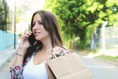 Young woman with shopping bags using smartphone stock photography