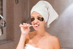 Portrait of a beautiful young woman after shower in patches. female brush teeth in front of her bathroom mirror. healty wellness. Morning concept royalty free stock photography