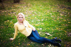 Portrait of beautiful young woman  sits on green grass, natural background Royalty Free Stock Images