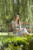 Portrait of beautiful young woman sitting on bench in park Royalty Free Stock Images