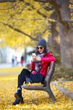 Beautiful young woman sitting in a bench and using her mobile phone in autumn. Royalty Free Stock Photos