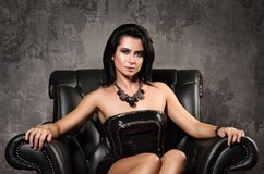 Portrait of beautiful young woman sitting in a black leather chair. The luxury and comfort. Black evening dress and necklace on her neck. Concrete wall in the Royalty Free Stock Images