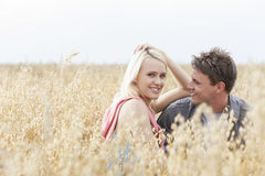 Portrait of beautiful young woman sitting with boyfriend amidst field Royalty Free Stock Image
