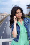 Portrait of beautiful young woman sitting on the bridge over the highway  and talking on the phone Royalty Free Stock Photo