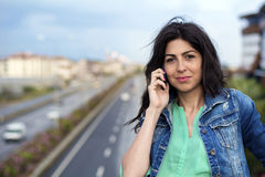 Portrait of beautiful young woman sitting on the bridge over the highway  and talking on the phone Stock Photos