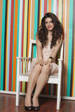 Portrait of a beautiful young woman sitting on chair against colorful striped background Stock Photography