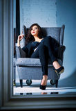 Portrait of beautiful young woman sitting on chair and looking into mirror Royalty Free Stock Image