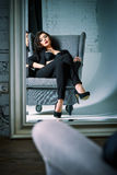 Portrait of beautiful young woman sitting on chair and looking into the mirror Royalty Free Stock Photo