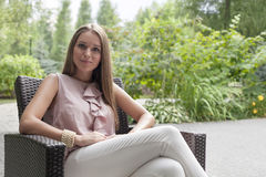 Portrait of beautiful young woman sitting on chair in summer park royalty free stock photography