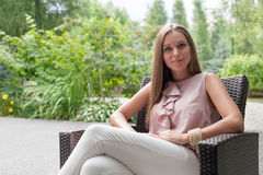 Portrait of beautiful young woman sitting on chair in summer park royalty free stock image